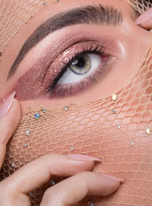 closeup of eye with metallic makeup and jewels