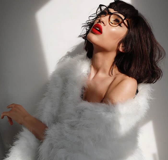 brunette with glasses wrapped in white fur
